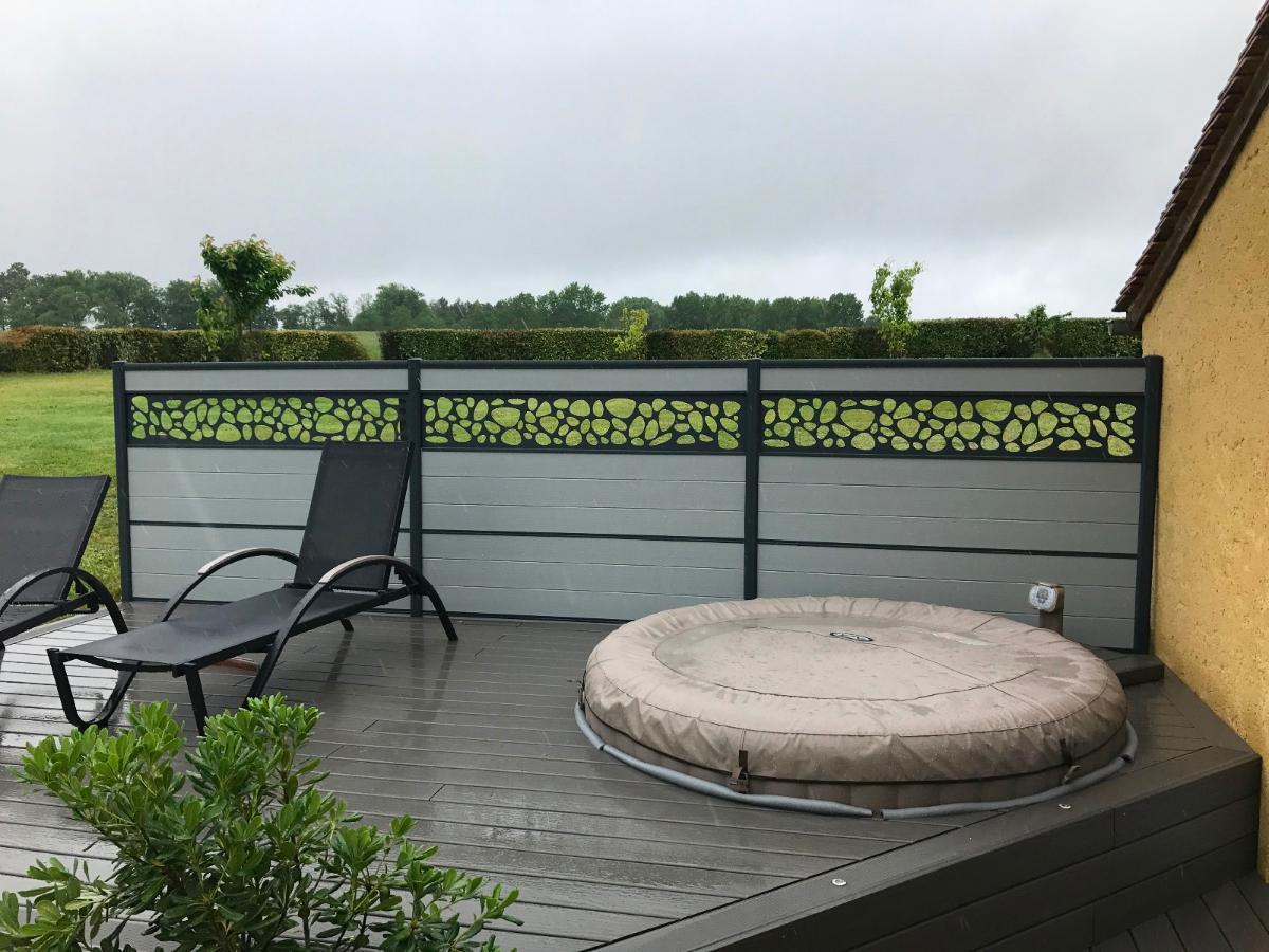 Intégration d'un spa sur une terrasse composite avec brise-vue ajouré.